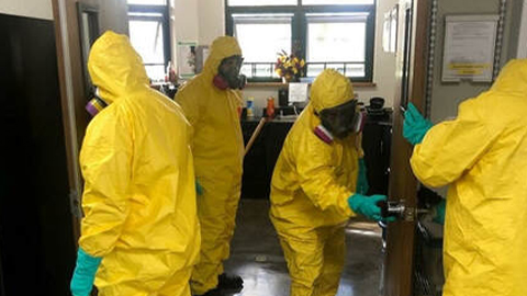 Four members of Patriot Environmental Services' COVID-19 decontamination response team decontaminate an office building