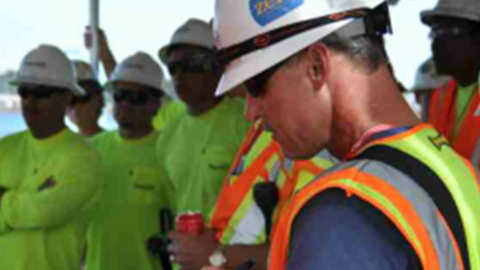 A Patriot Environmental Services field supervisor talks to his team about the waste cleanup project