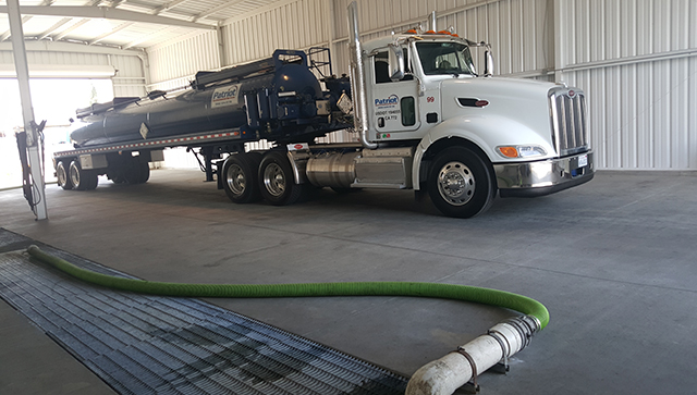 A Patriot Environmental Services vacuum tanker unloads waste and one of the company's wastewater treatment facilities