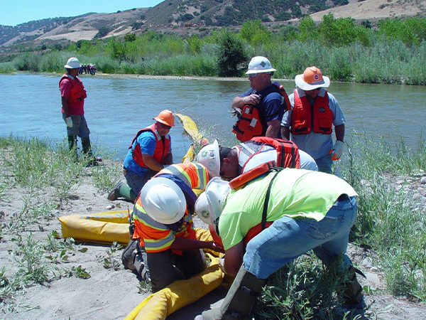 Patriot Environmental Services field technicians deploy boom to contain oil spilled in a river