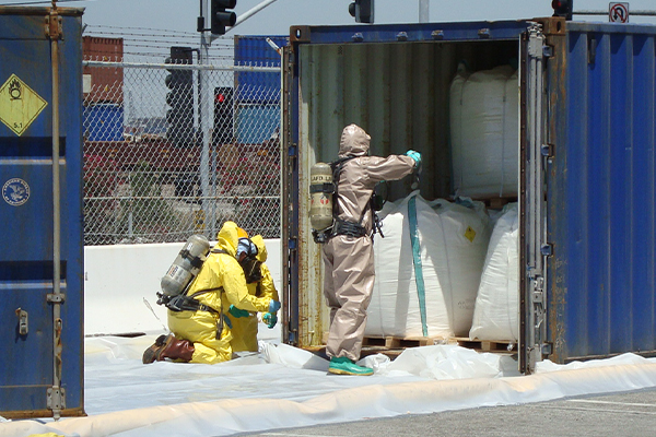 Three Patriot Environmental Services' employees wearing hazmat suits and SCBA tanks respond to a leaking shipping container