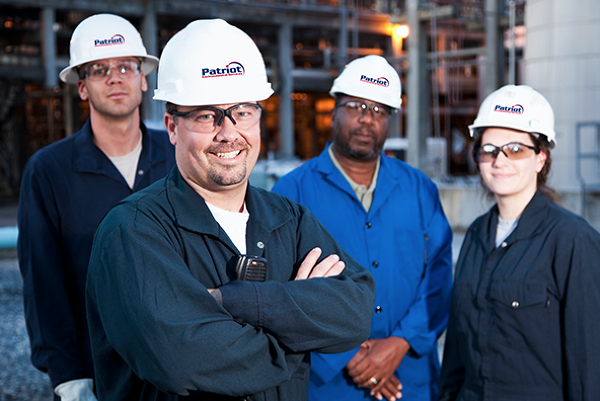 A diverse group of Patriot Environmental Services field technician wearing company uniforms and safety helmets