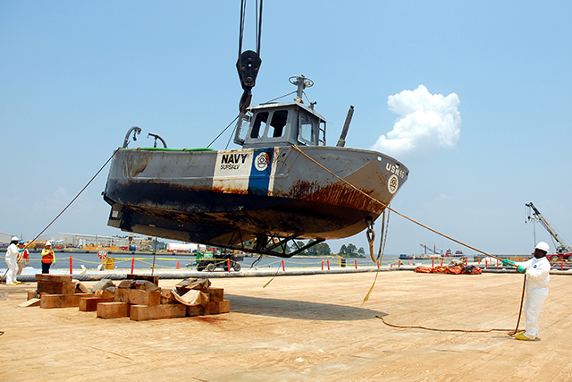 Patriot Environmental Services crews recovery a sunken U.S. Navy vessel from the harbor