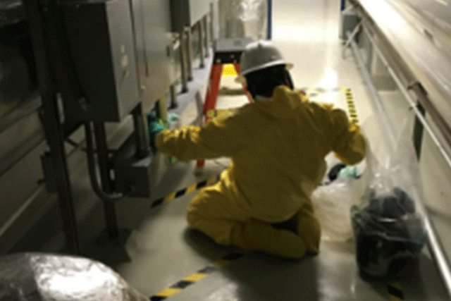 A Patriot Environmental Services technician performing decontamination work in a manufacturing facility