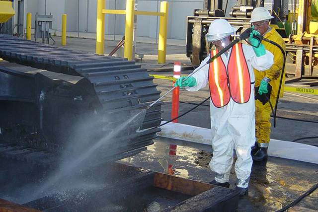 A Patriot Environmental Services technician hydro blasts a piece of mining equipment