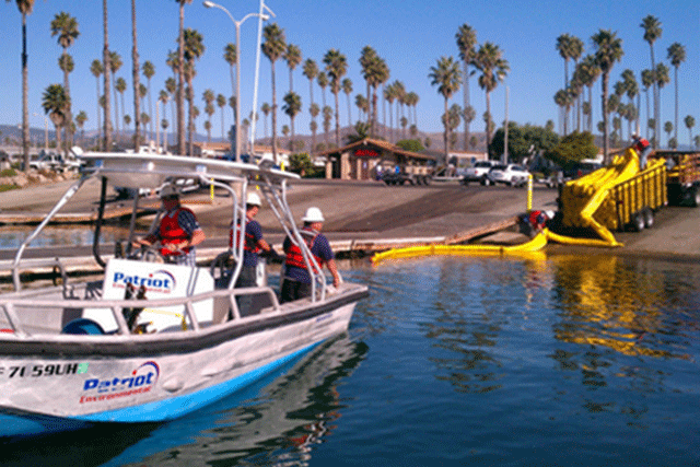 Patriot Environmental Services OSRO employees in a boat deploy containment boom during an inland water spill drill