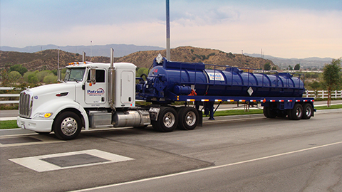 A Patriot Environmental Services specialized vacuum truck drives down the highway